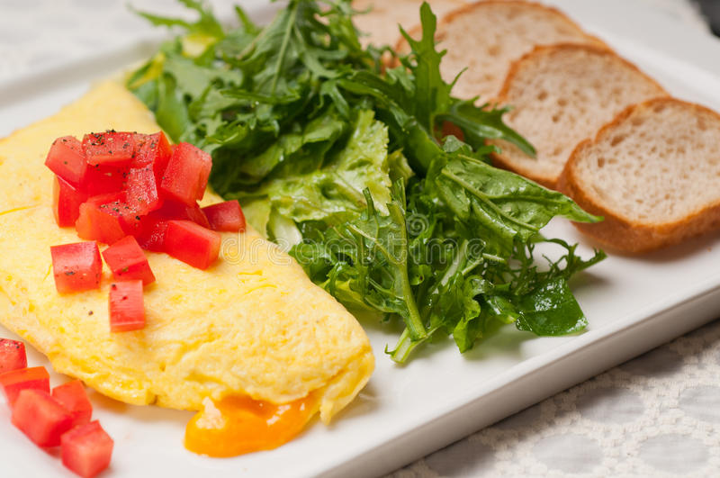 Cheese ometette with tomato and salad. Home made omelette with cheese tomato and rucola rocket salad arugola stock photo