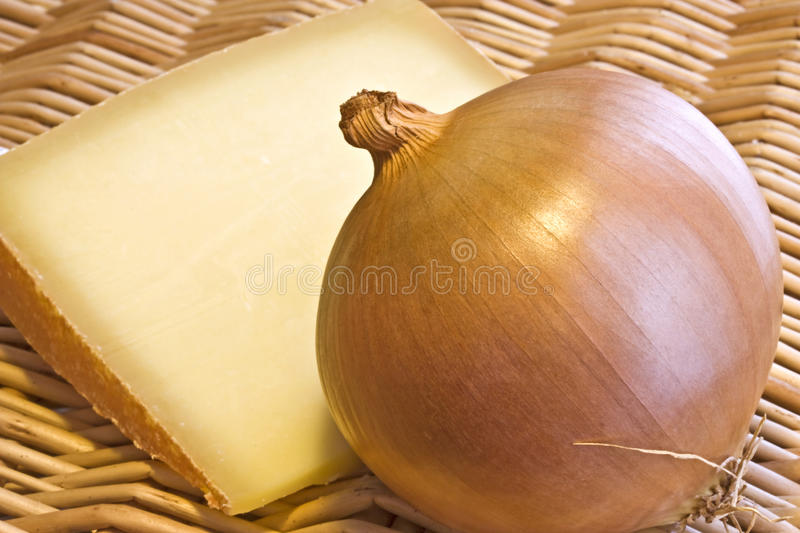 Onion and cheese. A close up of one onion and a slice of gruyere cheese on a wicker background stock photography