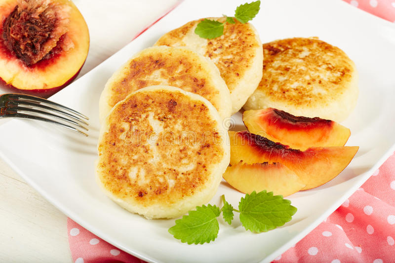 Cheese pancakes with peaches royalty free stock image