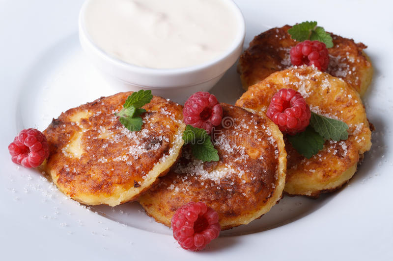 Cheese pancakes with raspberries and sour cream top view. Cheese pancakes with raspberries and sour cream on a white plate closeup. a horizontal top view royalty free stock photos