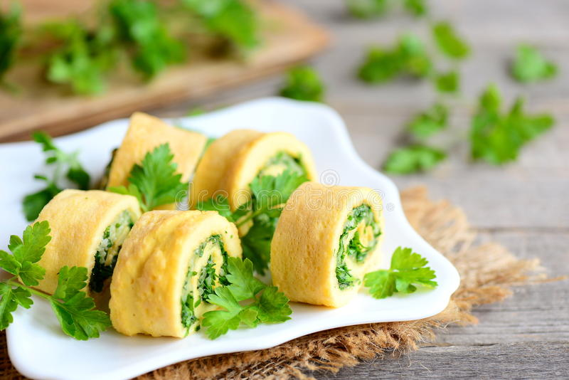 Cheese and parsley omelette rolls on a white plate. Home fried omelette rolls with grated cheese and finely chopped parsley stock photography