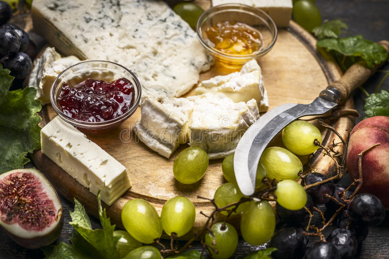 Cheese plate with Gorgonzola and Camembert cheese knife honey jam light and dark grapes a wooden cutting board close up royalty free stock photos