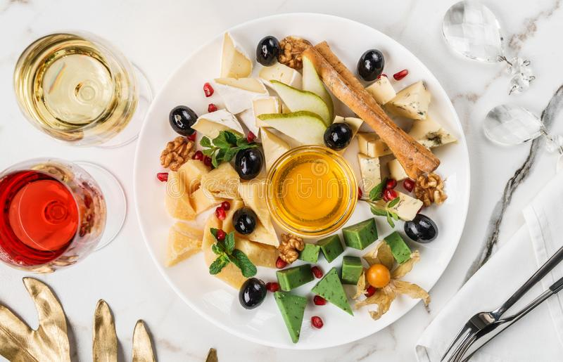 Cheese plate, green cheese, brie cheese served with wine, bread sticks and honey over light marble background. Snacks and Wine. Appetizers set, top view, flat royalty free stock photo