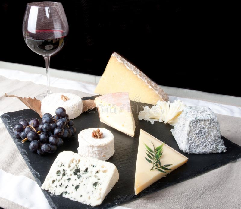 Cheese Plate with Red Wine, vine and Honey on black background stock photography