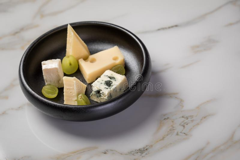 Cheese plate with selection Edamer, Parmesan, goat, blue and cream cheese, peer and grapes on black dish and marble background stock image