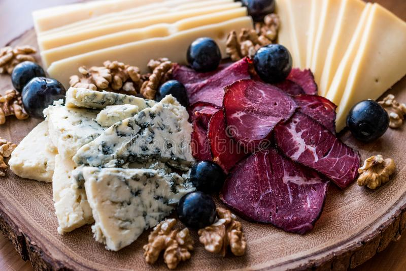 Cheese Plate with smoked meat, walnuts and grapes on wooden surface. stock photo