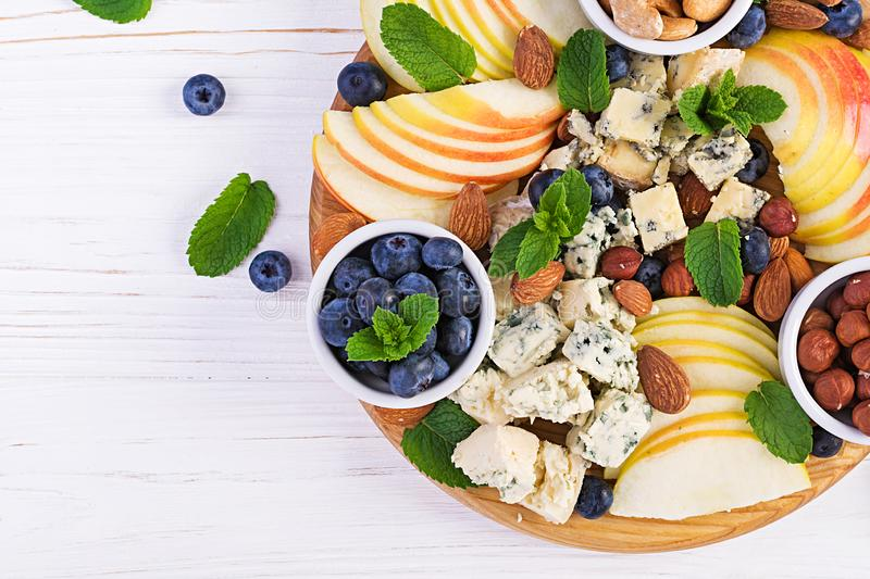Cheese platter with assorted cheeses, blueberry, apples, nuts on white table. stock photography
