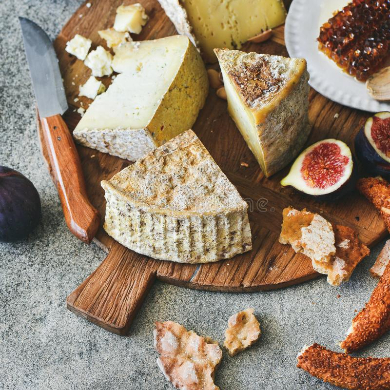 Cheese assortment, figs, honey, fresh bread and nuts, square crop. Cheese platter with cheese assortment, figs, honey, fresh bread and nuts on board over grey stock images