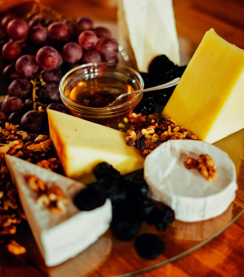 Cheese platter with different cheeses, grapes, nuts, honey, bread and dates on modern wooden background royalty free stock photo