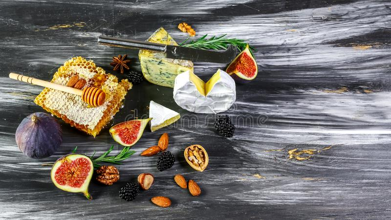 Cheese platter, figs and honey, snacks, on old wooden table. top view. copy space royalty free stock photo