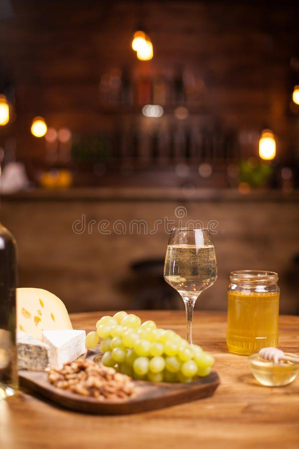 Cheese platter with fresh grapes and glasses of white wine on a rustic wooden table in a vintage pub. stock images