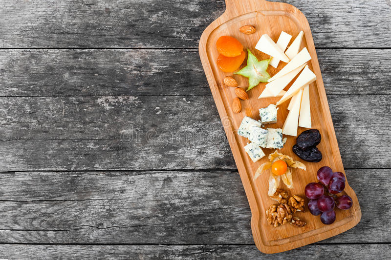 Cheese platter garnished with pear, honey, walnuts, grapes, carambola, physalis on cutting board on wooden background royalty free stock images