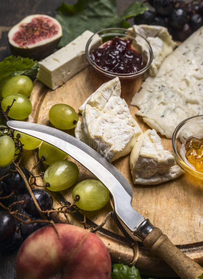 Cheese platter with Gorgonzola ,,Camembert and honey and jam, light and dark grapes peaches, knife for cheese on wooden cutting bo royalty free stock image