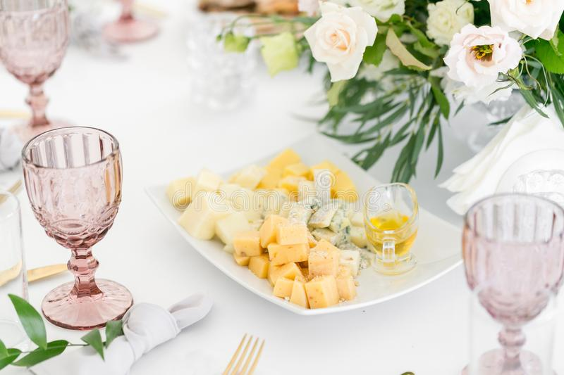Cheese platter. Plate with food on the table, snacks at the banquet, wedding banquet, table setting, dinner food, gala royalty free stock photo