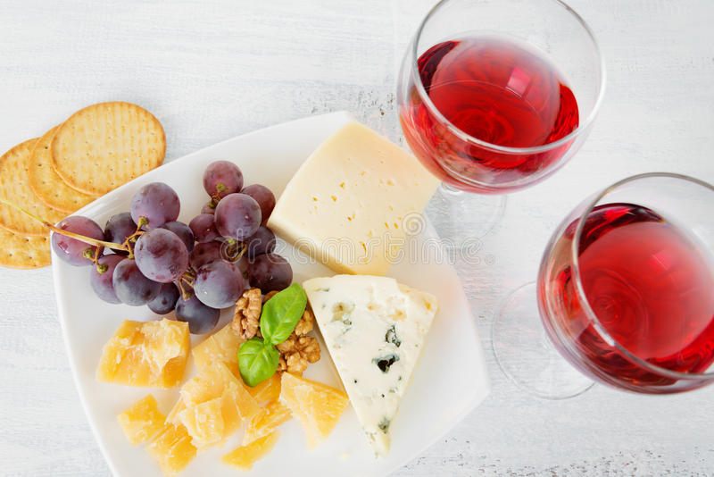 Cheese platter and two glasses of red wine royalty free stock image