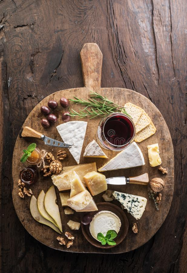 Free Cheese Platter With Organic Cheeses, Fruits, Nuts And Wine On Wooden Background. Top View. Tasty Cheese Starter Royalty Free Stock Photos - 141856078