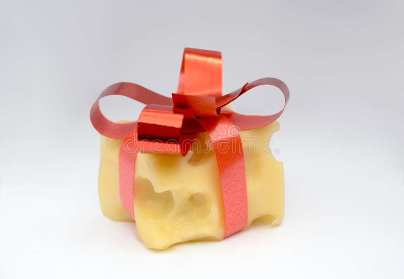 Cheese Present. Cheese cube decorated as gift. Cheese with big holes. It's decorated with red ribbons and bow on top and looks like a present. Shot over white stock photography