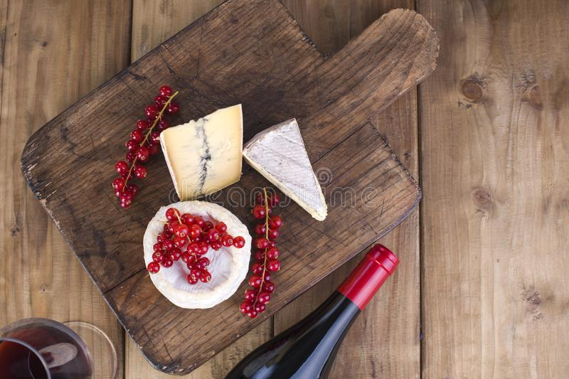 Cheese and red wine. Different cheese with white and blue mold. Berries of red currants White flowers. Wooden background and free royalty free stock photos