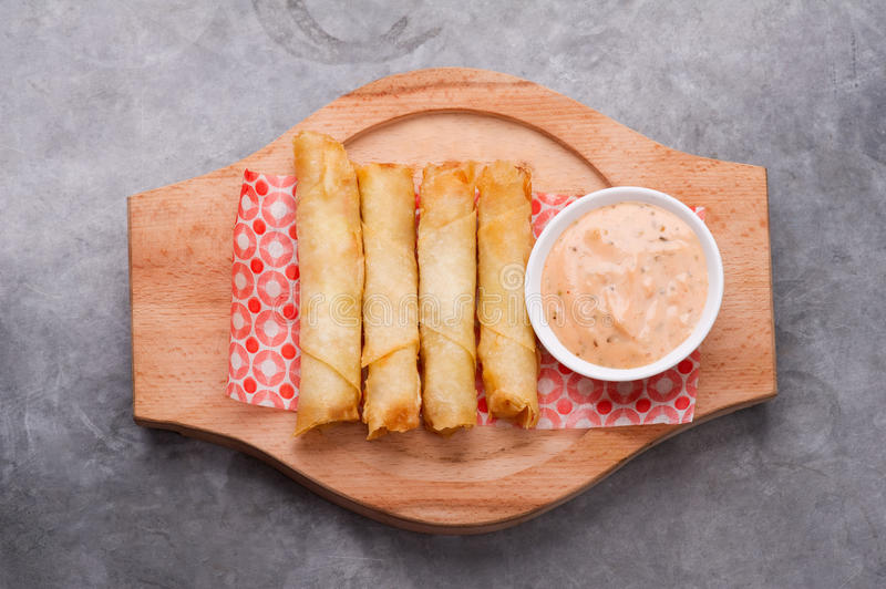 Cheese rolls plate with cocktail sauce served in a wooden plate on a rustic ba stock photography
