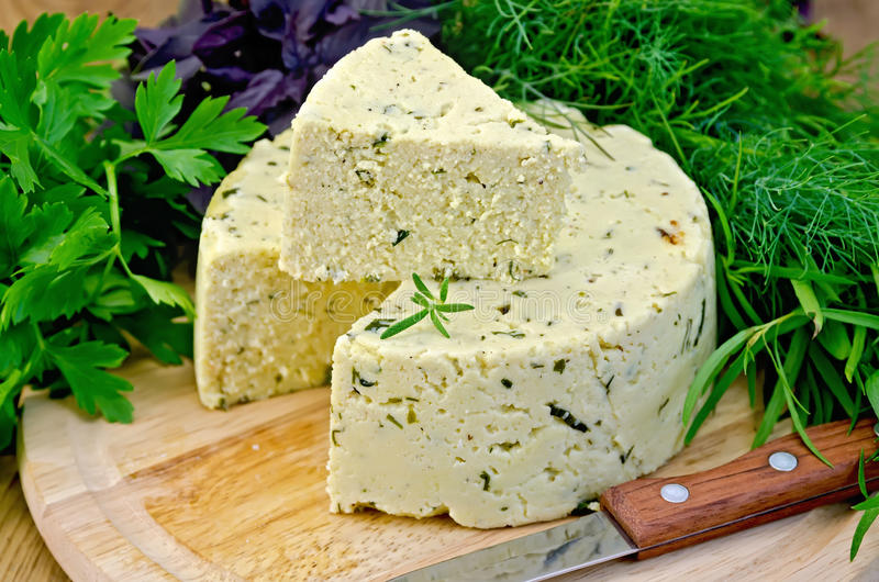 Cheese round homemade with herbs and knife on board stock photos