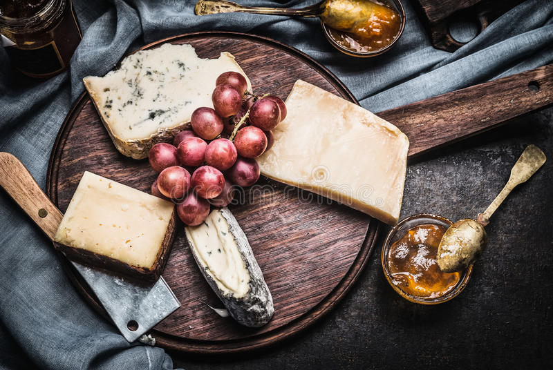 Download Cheese On Rustic Wooden Plate With Knife, Spoon And Sauces, Top View. Stock Photo - Image: 83700426