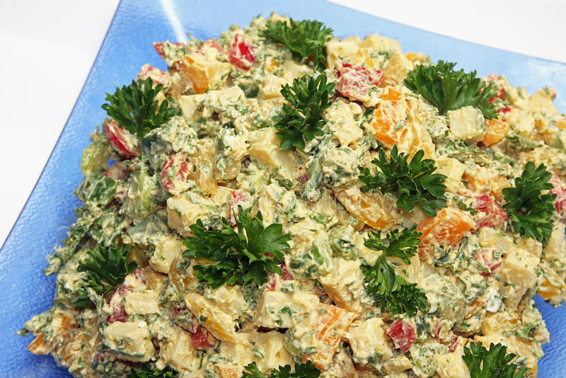 Cheese salad of cubed emmenthal cheese with parsley and dressing. On a glass plate royalty free stock photo