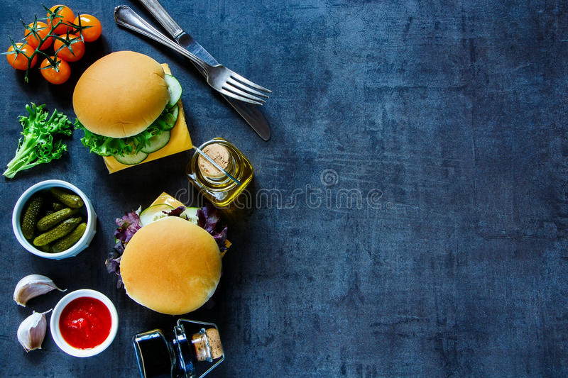 Cheese sandwich with vegetables. Freshly made cheese sandwiches with fresh vegetables on dark vintage background, border, top view, copy space. Vegetarian and royalty free stock photos