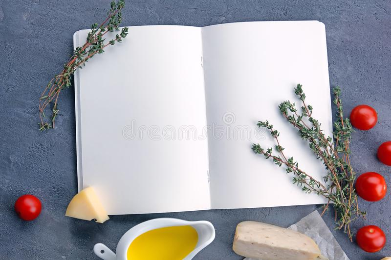 Cheese sauce with ingredients and blank notebook. On grey background stock photography