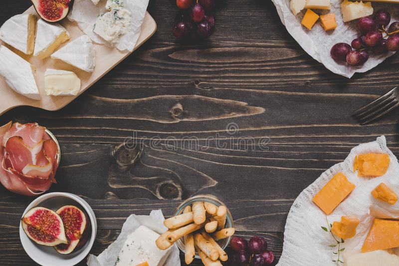 Cheese selection with fruits and snacks on the wooden dark table with copy space. Top view background stock photos