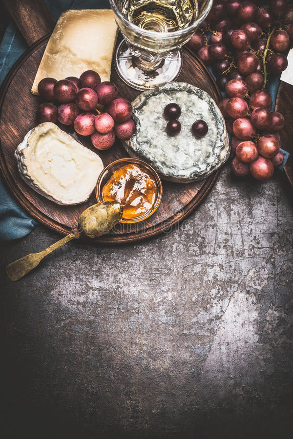 Cheese selection on rustic plate with wine, grape and Honey mustard sauce , dark vintage background, top view royalty free stock photography