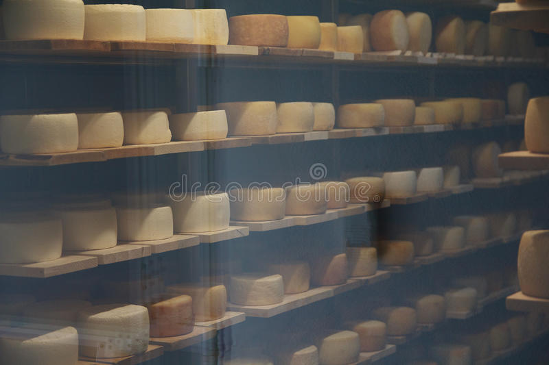 Cheese on shelves in the dairy room with temperature control. Of the glass royalty free stock photos