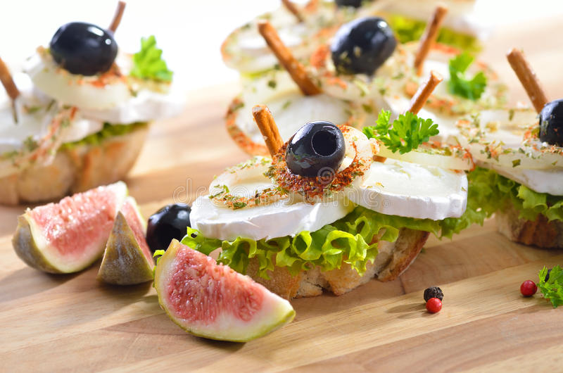 Cheese snack. Goat cheese on baguette with spiced onion rings, olives, lettuce and pretzel sticks royalty free stock image