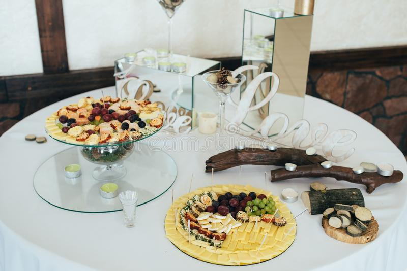 Cheese and snack buffet arrangement with various cheeses, wine, dressings, bread and snack food stock photos