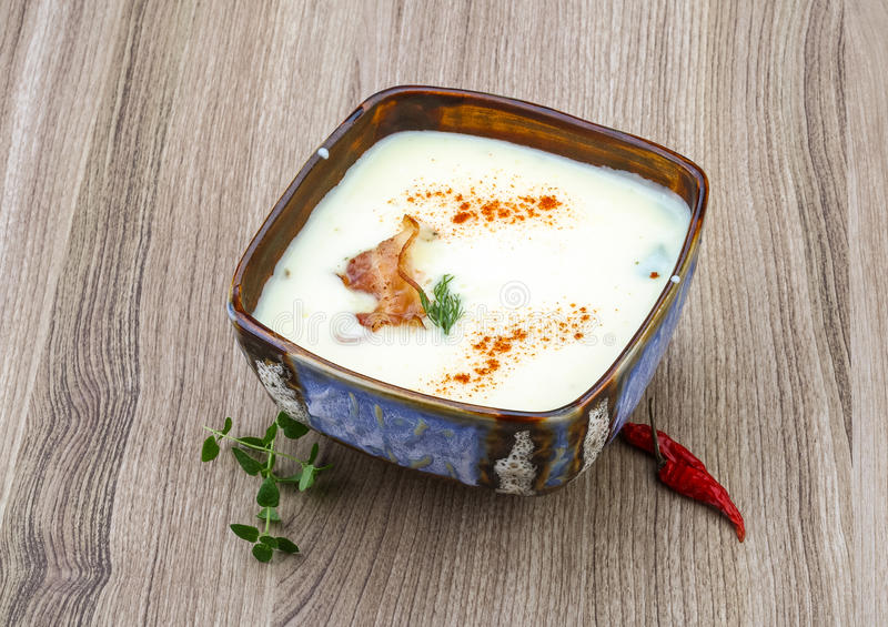 Cheese soup. With bacon and herbs on the wood background royalty free stock image