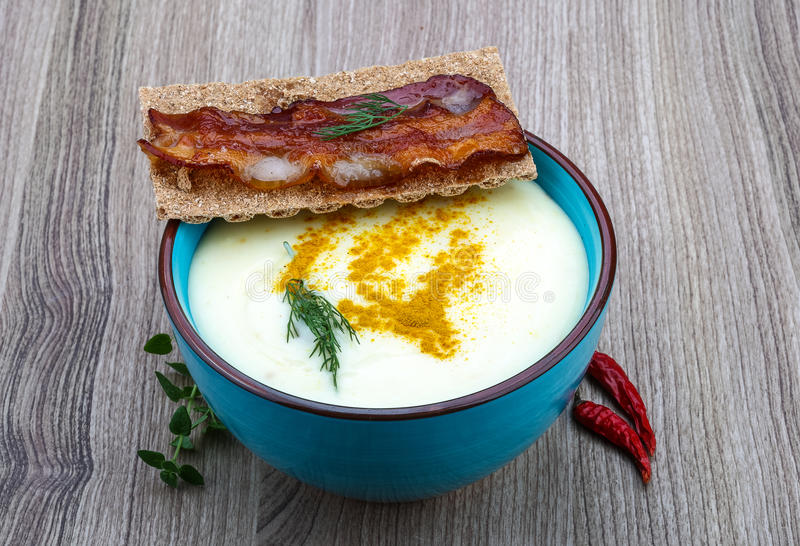 Cheese soup. With bacon and herbs on the wood background royalty free stock photo