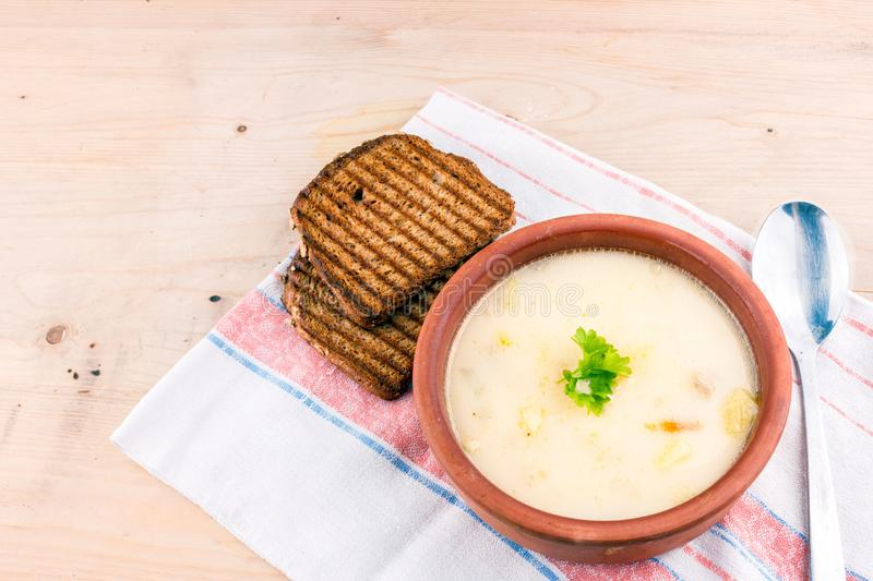 Cheese soup in a clay plate with toasted bread stock photos