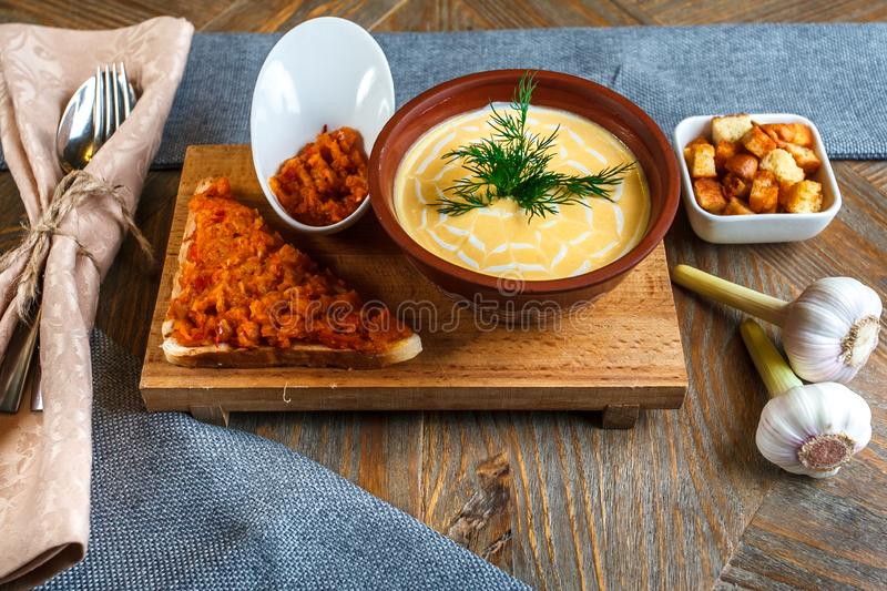 Cheese soup mashed in a clay plate is on a tray. Next to him is a piece of bread, a spoon and toast in a plate royalty free stock photography