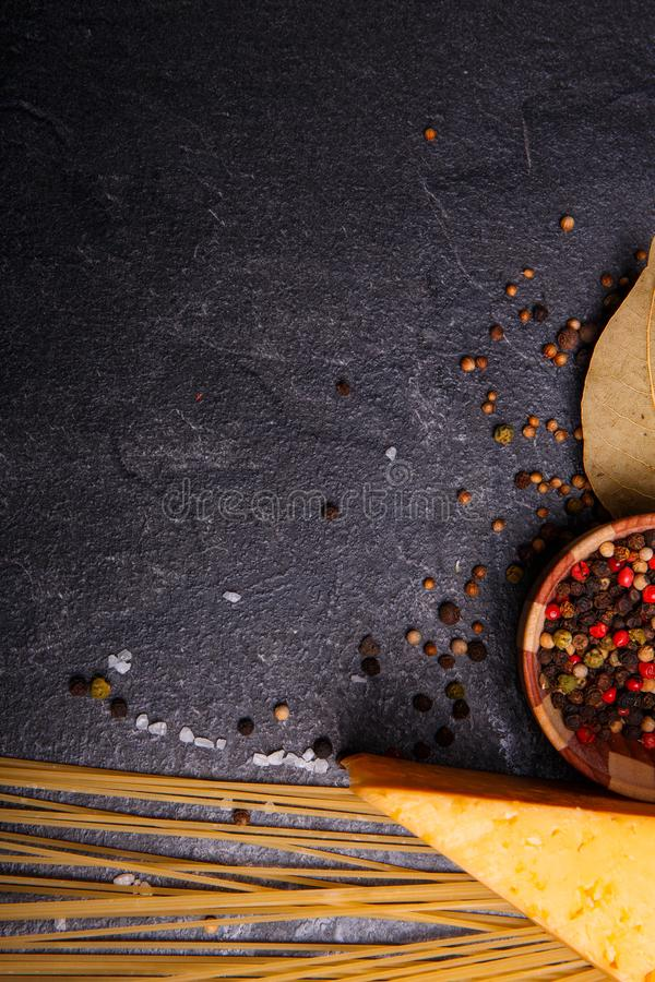 Cheese, spices, spaghetti on a black concrete background, free space for text. stock images