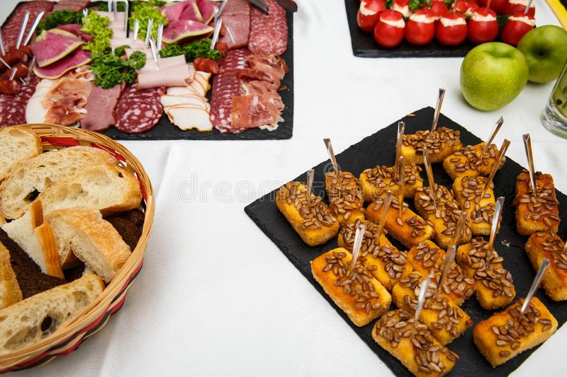 Cheese sticks. Food tray with delicious salami, pieces of sliced ham, sausage, salad. Bread. Tomatoes stuffed with cheese and garl stock image