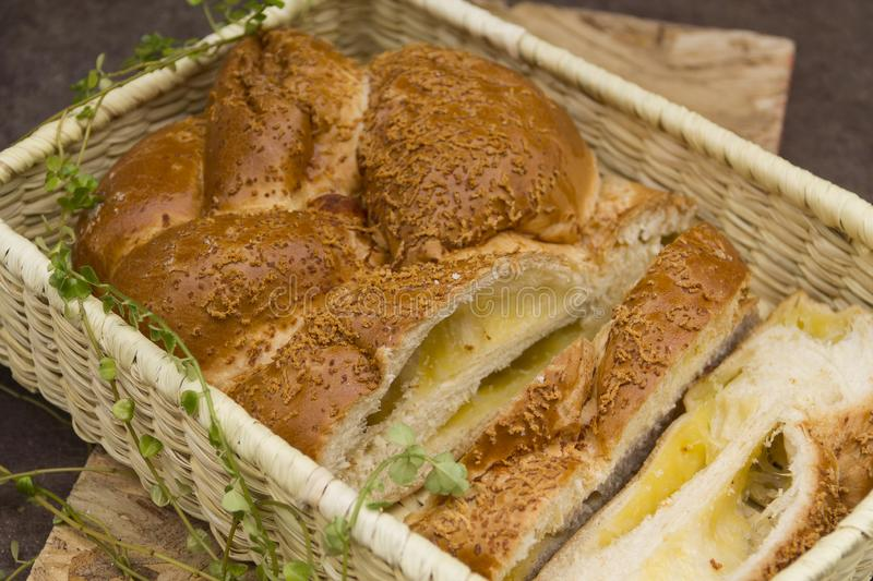 Cheese stuffed bread in wicker basket cut into handmade slices stock images