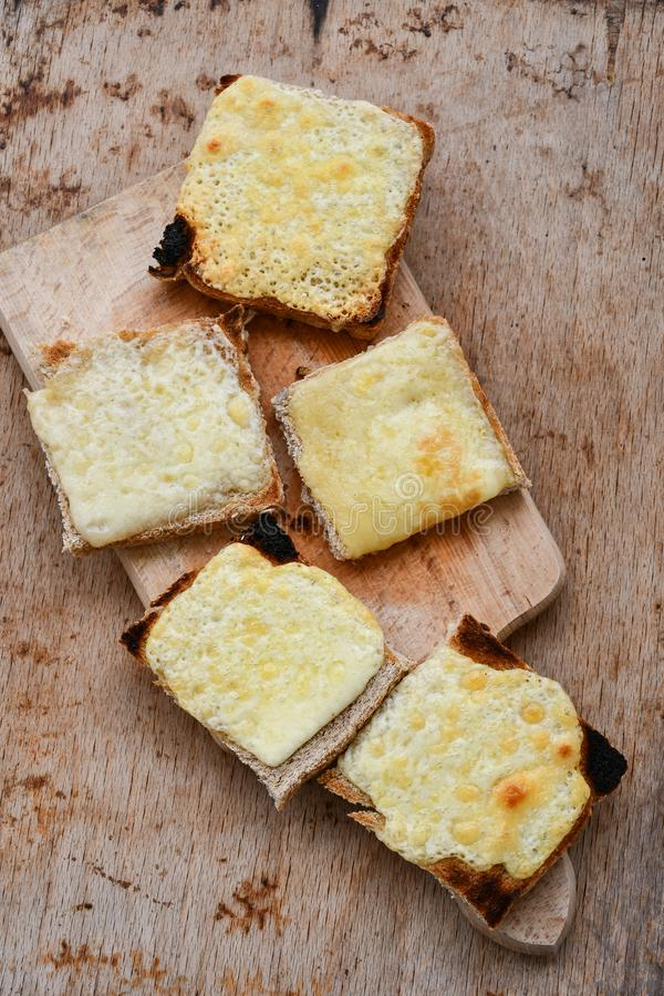 Cheese toast. Yellow cheese hot toast on wooden background stock image