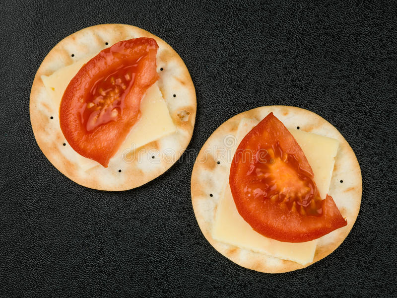 Cheese and Tomato on Water Biscuit Crackers royalty free stock photography