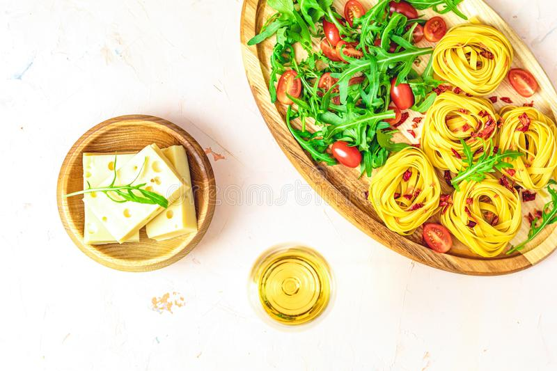 Cheese, tomatoes and arugula on the wooden plates. Delicious appetizer with white wine on the pink concrete table surface. op view stock image
