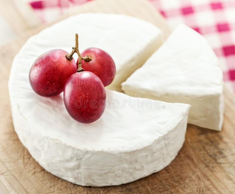 Cheese wheel with a piece of cheese on a wooden board with fruit royalty free stock photography