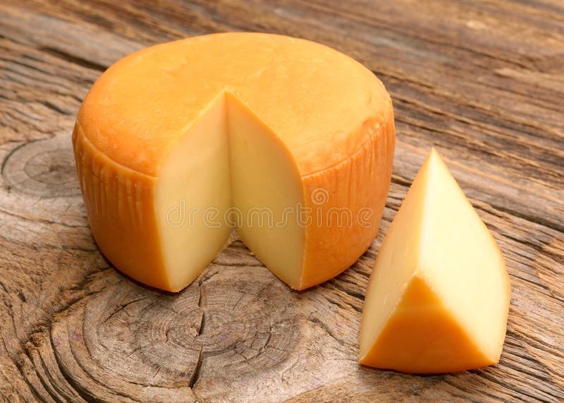 Cheese wheel on wooden table stock images