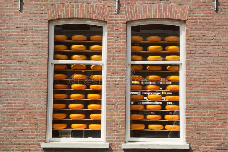 Cheese wheels in a Dutch shop windows. Traditionals cheese wheels stacked on shelves behind old-fashioned store windows in Delft, the Netherlands stock photo