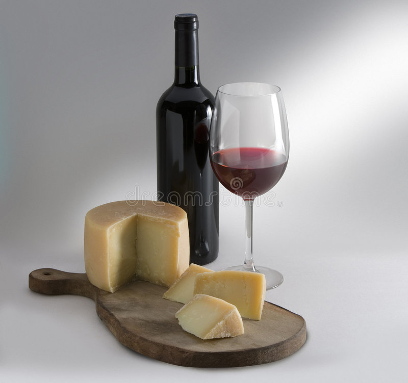 Cheese and wine. Cheese on board with wine cup and bottle