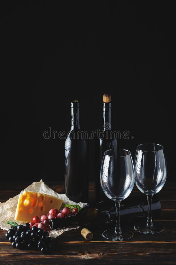 Cheese wine and bunches of grapes on a black background royalty free stock photos