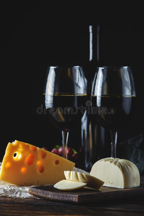 Cheese wine and bunches of grapes on a black background stock photo