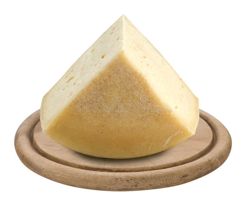 Cheese on wooden plate. Piece of italian cheese Montasio on a wooden plate royalty free stock image
